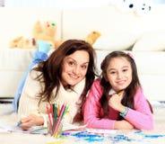 Mädchen zeichnet mit seiner Mutter Lizenzfreie Stockbilder