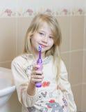 Schönes Mädchen zeigt eine elektrische Zahnbürste im Badezimmer Lizenzfreie Stockfotografie