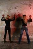Schönes Mädchen zwei, das eine alte Wand bereitsteht lizenzfreie stockfotos
