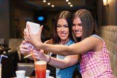 Schönes Mädchen zwei, das Spaß mit intelligentem Telefon hat Lizenzfreie Stockbilder