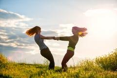 Schönes Mädchen zwei, das Spaß zusammen zur Sonnenuntergangzeit hat lizenzfreie stockfotos