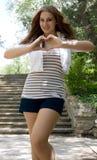 Schönes Mädchenerscheinen-Liebeszeichen im Freien Stockfotos