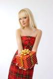 Schönes Mädchenholding-Weihnachtsgeschenk im roten Kleid Lizenzfreie Stockfotografie