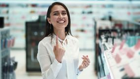 Schönes Mädchenkäuferlachen und -lächeln in den Kosmetik kauft, Zeitlupe stock video footage