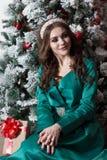 Schönes Mädchenmodell in einem grünen Kleid, das nahe einem verzierten Weihnachtsbaum mit ihren Händen auf ihren Knien sitzt Neue Stockfotos