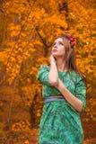 Schönes Mädchenmodell im gelben Herbstlaub Stockfotografie