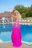 Schönes Mädchenmodell im rosa Modekleid, das durch blaues outdoo aufwirft Stockfotos