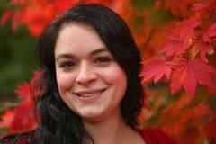 Schönes Mädchenporträt im roten Herbstlaub Stockfotografie