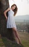 Schönes Mädchenporträt mit Hut nahe einem Baum im Garten. Junge kaukasische sinnliche Frau in einer romantischen Landschaft. Geumg Lizenzfreie Stockfotografie