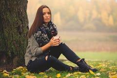 Schönes Mädchenstillstehen und trinkender Kaffee sitzend im Herbstgarten Stockbilder