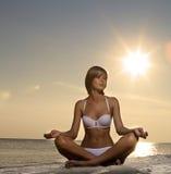 Schönes Mädchenyoga auf dem Strand am Sonnenuntergang Lizenzfreie Stockfotos