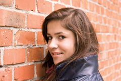 Schönes Mageres des jungen Mädchens auf roter Backsteinmauer Lizenzfreies Stockfoto