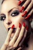Schönes Make-up und lange rote Nägel stockbild