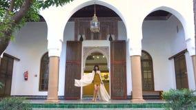 Schönes marokkanisches Mädchen, das ihren hellen weißen Umhang in malerischem Dar Si Said Riyad in Marrakesch an der Sonnenunterg stock footage