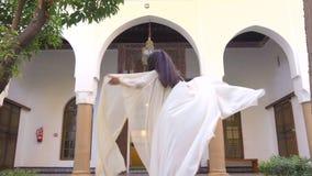 Schönes marokkanisches Mädchen, das ihren weißen Umhang in malerischem Dar Si Said Riyad in Marrakesch bei Sonnenuntergang spinnt stock video
