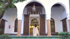 Schönes marokkanisches Mädchen, das ihren weißen Umhang in malerischem Dar Si Said Riyad in Marrakesch an der Sonnenuntergangzeit stock video