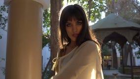 Schönes marokkanisches Mädchen, das ihren weißen Umhang in malerischem Dar Si Said Riyad in Marrakesch an der Sonnenuntergangzeit stock footage