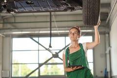 Schönes Mechanikermädchen überprüft das Rad lizenzfreie stockfotografie