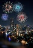 Schönes mehrfaches Feuerwerk, das über der Fluss-Stadt explodiert Lizenzfreie Stockfotos
