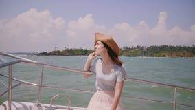 Schönes mittleres geschossenes Porträt der glücklichen jungen schönen touristischen Frau, die im Sonnenhut auf Seeyachtsegeln auf stock video