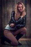 Schönes Mode-Modell mit dem blonden gelockten Haar, das schwarze Jacke, Hosen und schwarze hohe Stiefel in einer Haltung auf ihren Stockfoto
