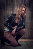 Schönes Mode-Modell mit dem blonden gelockten Haar, das schwarze Jacke, Hosen und schwarze hohe Stiefel in einer Haltung auf ihren Stockbilder