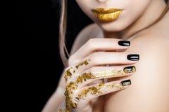 Schönes Modefrauenmodell-Gesichtsporträt mit Goldlippenstift und schwarzen Nägeln Zaubermädchen mit hellem Make-up schönheit Stockbild