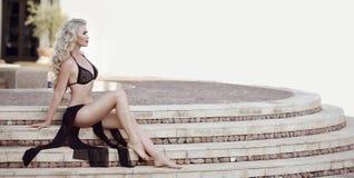 Schönes Modell der eleganten Frau im schwarzen Bikini, der auf staircas aufwirft Stockbilder