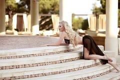 Schönes Modell der eleganten Frau im schwarzen Bikini, der auf staircas aufwirft Stockbild