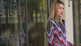 Schönes Modell der modernen Frau, das nahe Luxusgebäude aufwirft stock video