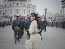 Schönes Modell geht die Stadt in einem weißen Kleid Stockbild