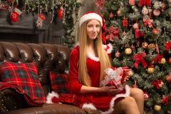 Schönes Modell gekleidet als Sankt mit nahe einem Weihnachtsbaum Lizenzfreies Stockfoto