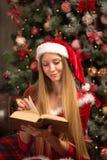 Schönes Modell gekleidet als Sankt mit nahe einem Weihnachtsbaum Lizenzfreie Stockfotos