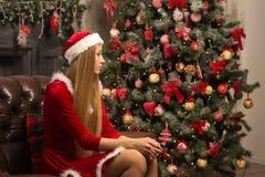 Schönes Modell gekleidet als Sankt mit nahe einem Weihnachtsbaum Lizenzfreies Stockbild