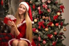 Schönes Modell gekleidet als Sankt mit nahe einem Weihnachtsbaum Lizenzfreie Stockfotografie