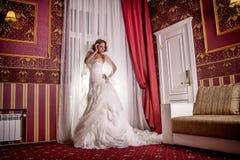 Schönes Modell im Hochzeitskleid, das freundlich in der Bewegung in der Studiofotosession aufwirft stockbilder