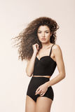 Schönes Modell mit dem Fliegen des gelockten Haares in der schwarzen Unterwäsche, die Kamera betrachtend aufwirft Stockfotos