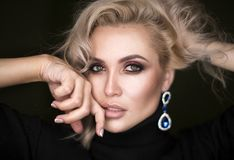 Schönes Modell mit dem gelockten blonden Haar auf schwarzem Hintergrund Stockfoto