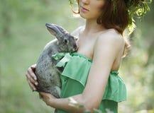Schönes Modell mit einem grauen Kaninchen in ihren Armen Lizenzfreie Stockfotos