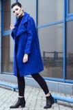 Schönes Modell mit perfektem bilden und das Haar, das zurück in ein Brötchen ausrangiert wird, das in modischen blauen Mantel geh stockbilder