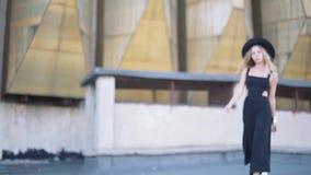 Schönes Modemädchen im schwarzen Kleid, das an der Kamera auf städtischem Architekturhintergrund aufwirft und lächelt stock footage