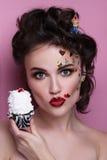 Schönes Modemädchen mit Luxusberufsmake-up und lustigen emoji Aufklebern geklebt auf dem Gesicht Junge Frau mit kleinem Kuchen Stockbilder