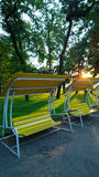 Schönes modernes Bankschwingen in einem allgemeinen Park der Stadt bei Sonnenuntergang Vertikale Ansicht Lizenzfreies Stockbild
