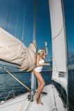Schönes modernes blondes Mädchen im Bikini und das T-Shirt, das auf einer Yacht aufwirft, versenden Stockfotografie