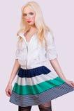 Schönes modernes blondes Mädchen im Rock mit Streifen Stockfotografie