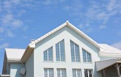 Schönes modernes Haus mit weißen Wänden, weißen Dachplatten und großen panoramischen Hauptdachbodenfenstern stockfotografie