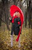 Schönes modernes junges Mädchen mit rotem Regenschirm, roter Kappe und rotem Schal im Park Lizenzfreies Stockfoto