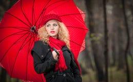 Schönes modernes junges Mädchen mit rotem Regenschirm, roter Kappe und rotem Schal im Park Stockfotografie