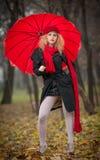 Schönes modernes junges Mädchen mit rotem Regenschirm, roter Kappe und rotem Schal im Park Stockbild