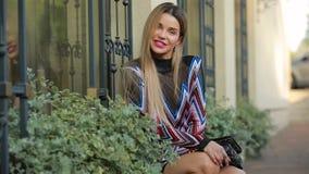 Schönes modernes Luxusfrauenmodell, das Sitzen nahe Gebäudeäußerem aufwirft stock video